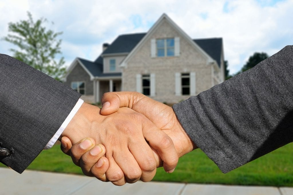two hands shake to make an offer on a home